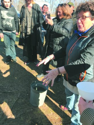 Naturalist Carol Fink from the Farmington Hills Nature Center explains how to collect sap.