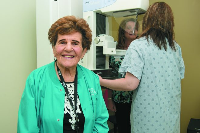 Fay Jacobs, a 93-year-old volunteer at Karmanos Cancer Institute's Weisberg Cancer Treatment Center, helps women prepare for their mammograms at the Farmington Hills-based center. Also pictured is Lisa Abele, lead mammographer at Weisberg, and a patient. Karmanos volunteer