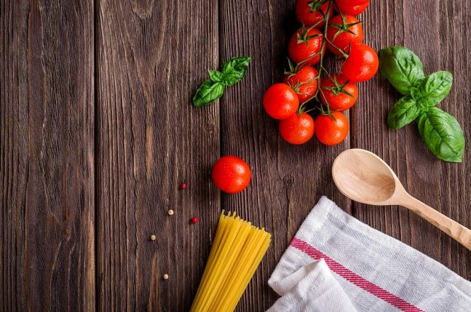 stock image of pasta, tomatoes, basil, a wooden spoon and twoel for Rachel Hyam's new kosher cooking kitschy kosher cooking blog