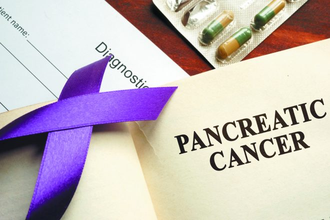 Pancreatic cancer written on a page and  purple awareness ribbon.
