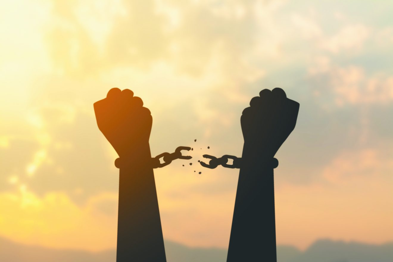 silhouette hand with chain is absent and blurred sky in sunrise background representing the freedom of the Jews from their shackles during Pesach.