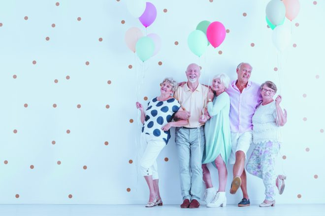 Happy older people smiling and standing with colorful balloons at the New Year's Eve party photo
