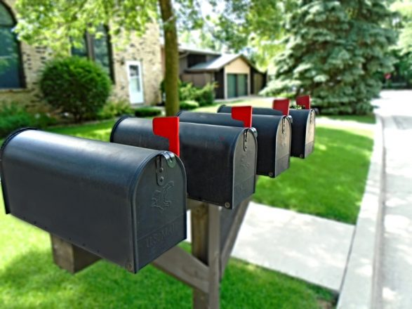 four mailboxes with flags up indicating they have mail in them on a street by a house with a lot of greenery.