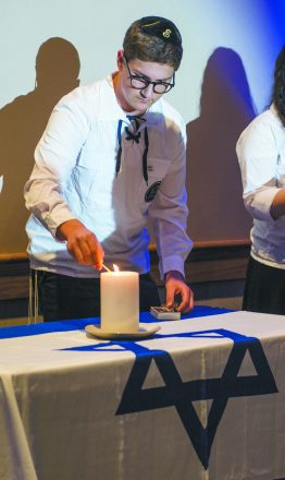 Ethan Adler, 16, of Southfield lights a candle in memory of those who died in service to Israel.