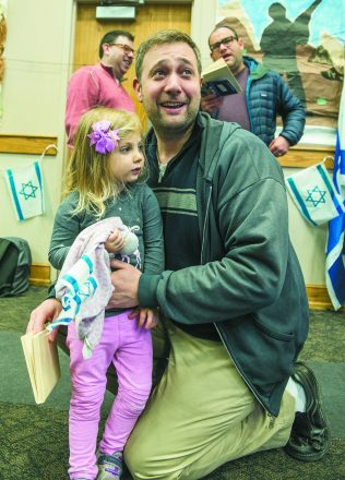 Josh Younger and his daughter, Hanna, 3, watch the festivities.