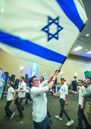 Ezra Klausner of Southfield waves the flag of Israel as the men and students dance around him. Celebrating Israel's 70th Anniversary for Israel@70