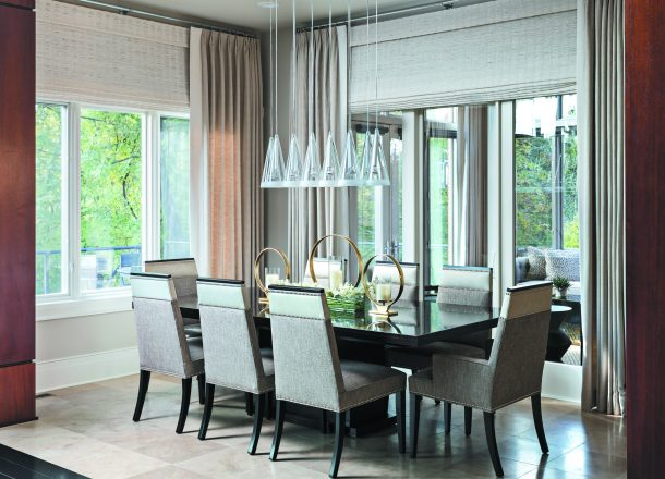 "The airy dining room, which looks out to the sunroom, was made to appear even taller: King added two layers of drapes and woven Roman shades to cover a foot and a half of drywall. ""Taking it all the way to the ceiling makes the windows appear much taller,"" he says. Travertine floors from CIOT in Troy add elegance underfoot to the neutral warmth of the room. A length of leather tops the fabric-covered chairs."