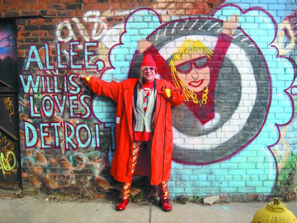 Allee Willis poses in front of a mural of herself, painted by a fan.