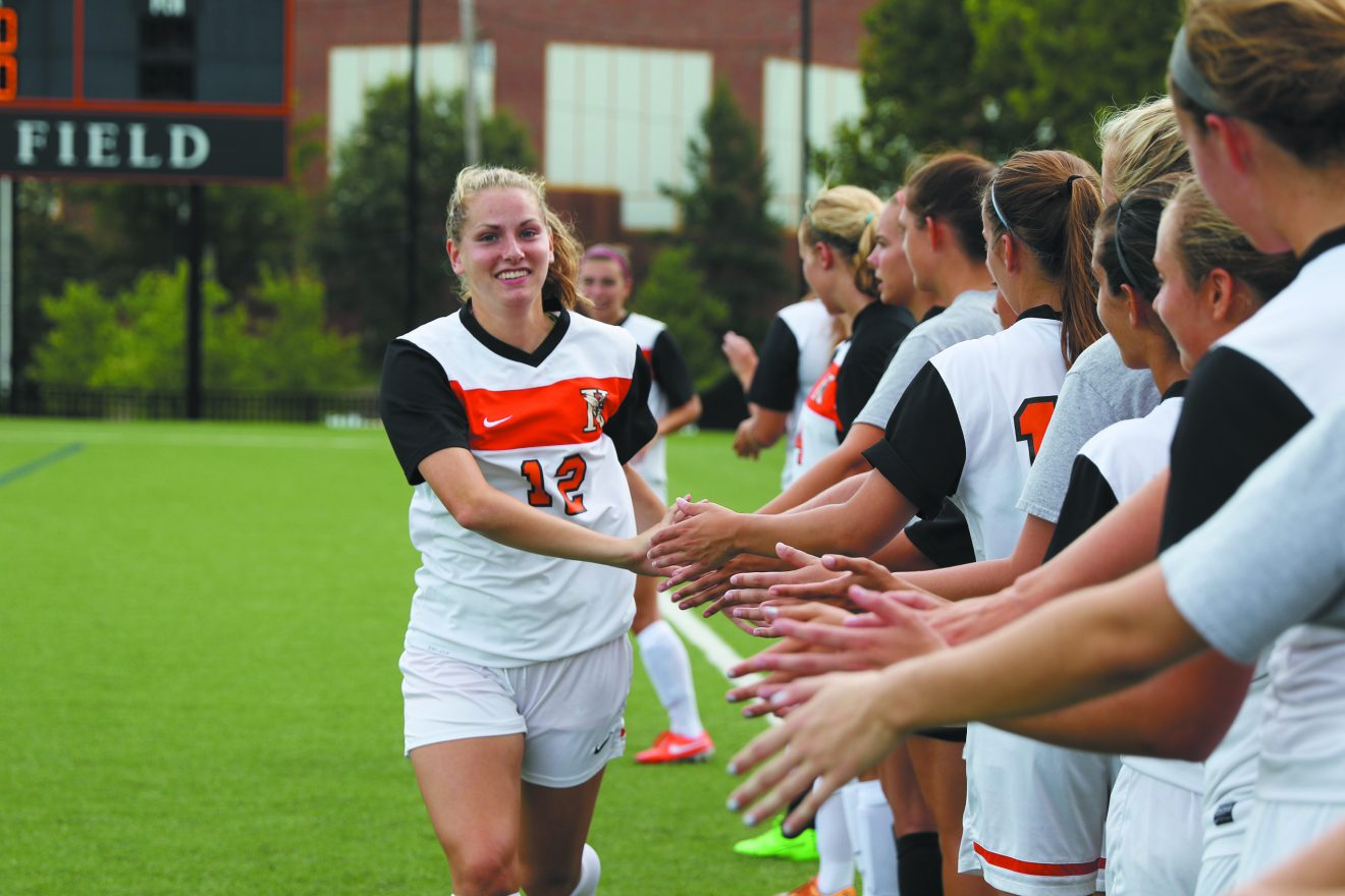 Allie Brodsky, a two-year captain of the Kalamazoo College women's soccer team, is greeted by teammates.