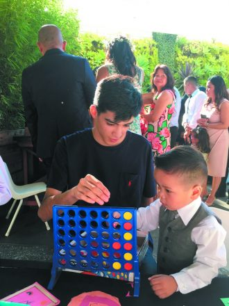 A Black Tie Kids counselor plays Connect Four at a wedding.