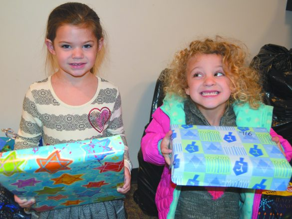 Now: Two young girls donating Chanukah gifts.