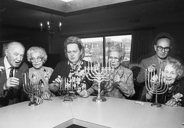Then: Older adults share Chanukah candle-lighting together.