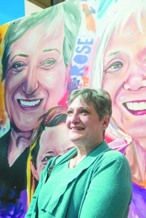 Rose Brystowski in front of her likeness on the Beaumont Hospital outdoor mural.