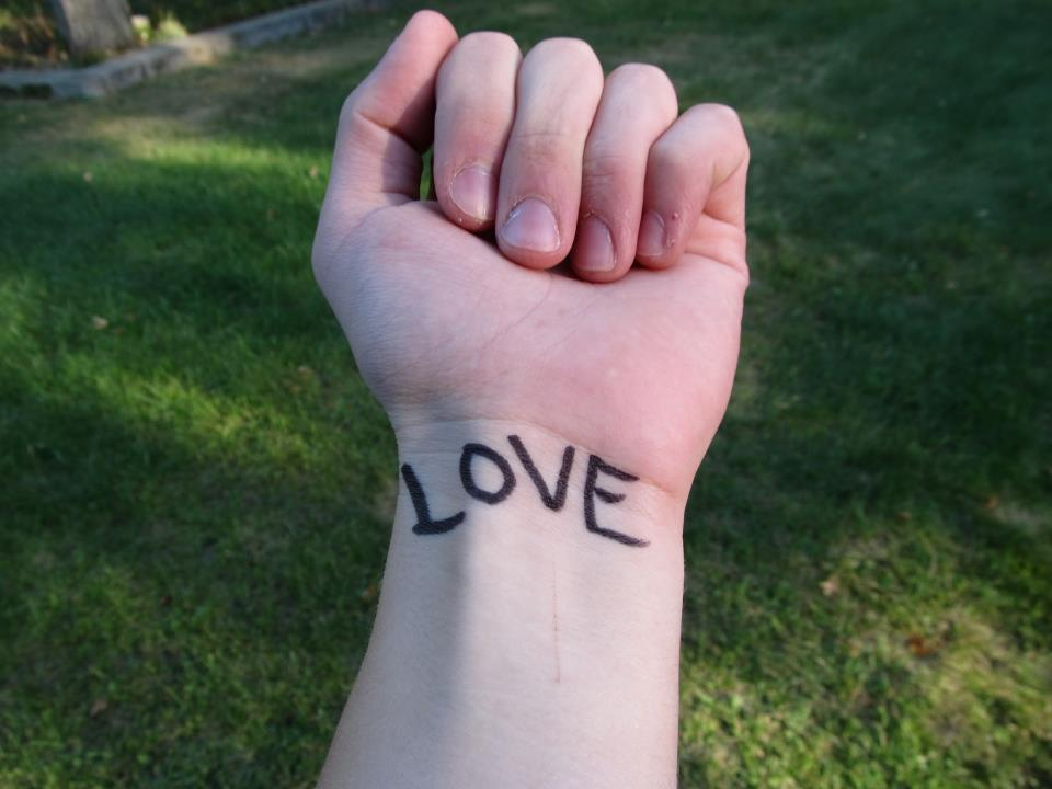 """love"" written on a person's wrist"