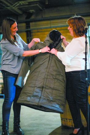 Lisa Lauter helps Lauren Knill of the Empowerment Project show a coat that turns into a sleeping bag. Photo by Anthony Lanzilote