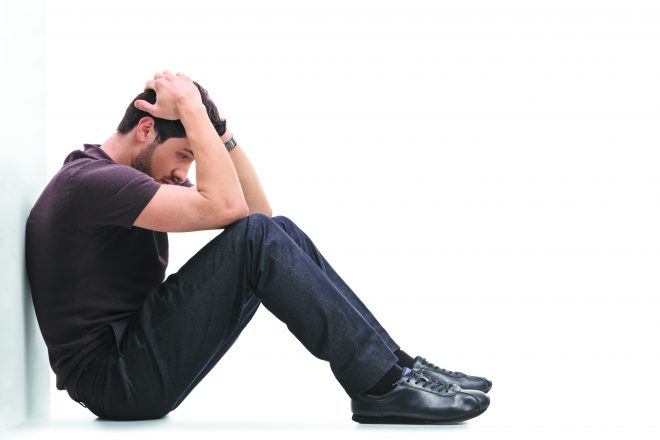 Depressed man sitting on the floor with his head down and leaning against a wall isolated on white background. Shows campus mental health and college health concerns