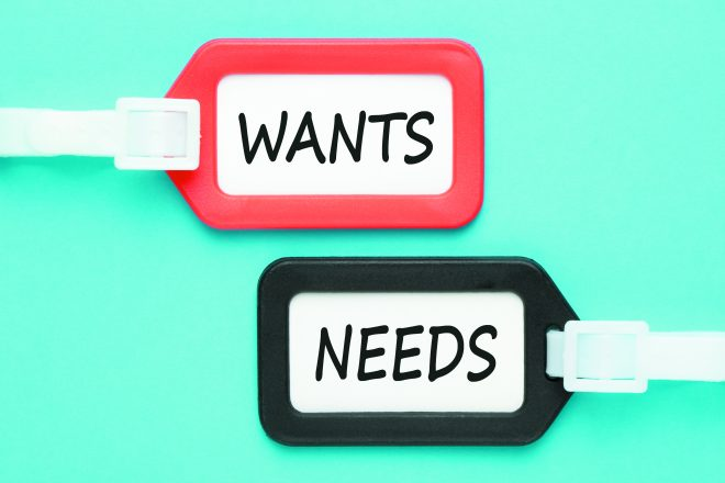 WANTS and NEEDS written on luggage tags on blue background. Business concept. Top view.