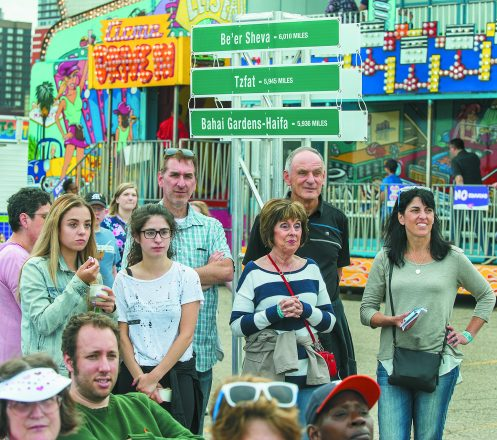 Israel@70. On the site of GM River Days, audience members listen to music amid road signs showing mileage to Israeli destinations.