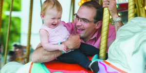Israel@70. Mila Schwartz, 1, of Plymouth enjoys a merry-go-round ride with her father, Jonathan.