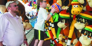 Israel@70. Aaron Leib watches as his son Meir, 5, attempts to win a stuffed animal in the basketball challenge.