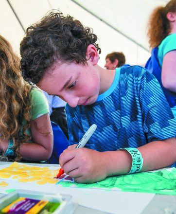 Israel@70. Eyal Tirosh, 7, of Israel enjoys the crafts tent, where many community organizations were represented.