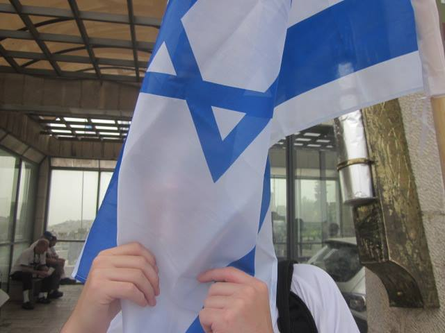 Stefani Chudnow hides behind an Israeli flag on a trip to Israel.