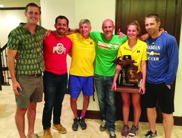 Coach Barry Brodsky (third from left) and assistant coach Allie Brodsky (holding trophy) celebrate the Birmingham Marian girls soccer team's latest state championship with assistant coaches (from left) Peter Hensoldt, Adam Gorski, Reid Friedrichs and Mike Schimmel.