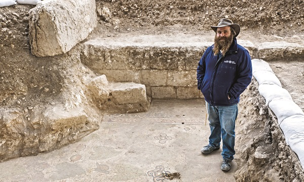 Archaeologist Benyamin Storchan stands on a Byzantine mosaic floor uncovered in Beit Shemesh.