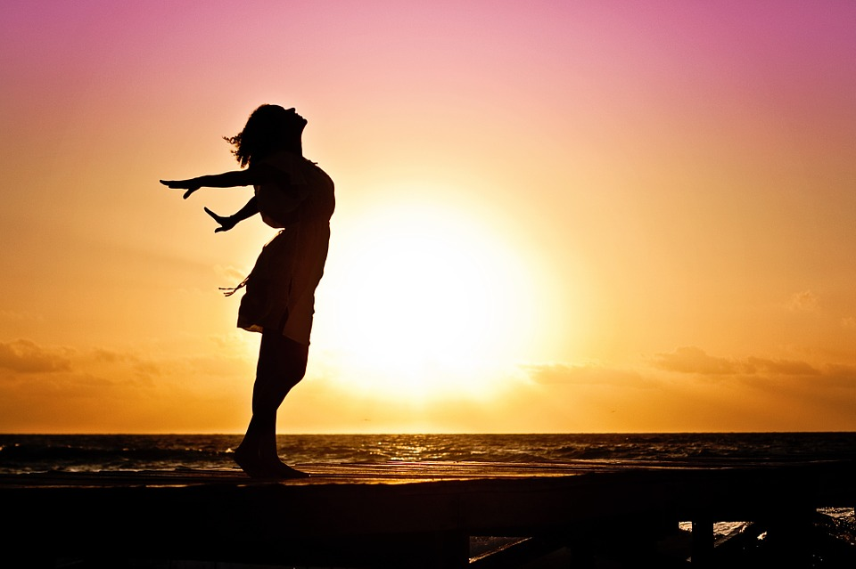 woman stands silhouetted before a sunset.