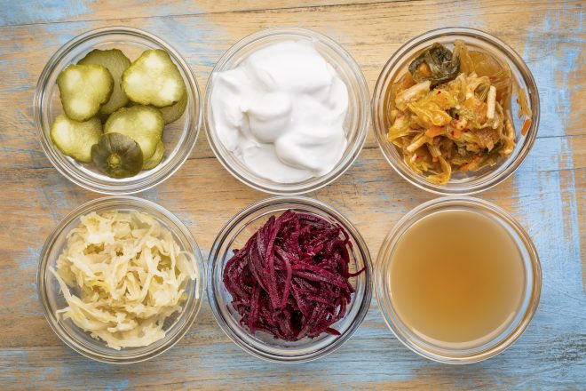 colon health food. a set of fermented food great for gut health - top view of glass bowls against grunge wood: cucumber pickles, coconut milk yogurt, kimchi, sauerkraut, red beets, apple cider vinegar