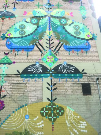 The mural includes folk symbols reminiscent of the artist's Eastern European Jewish roots.