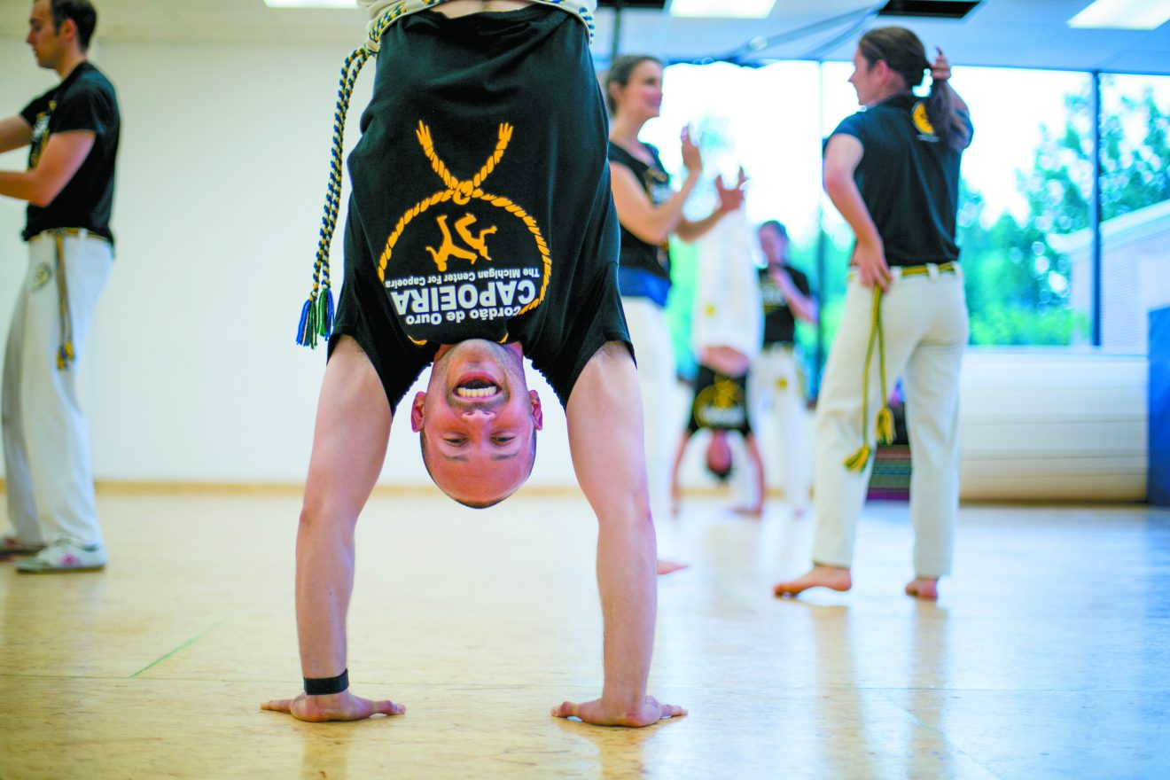 Capoeira Contra-Mestre Baz Michaeli demonstrates a handstand during a class at his Michigan Center for Capoeira in Farmington Hills.