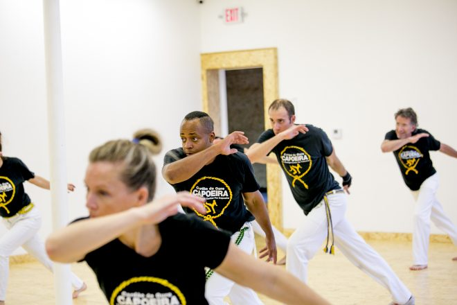 students train by doing Ginga, a mainstay move of the Brazilian martial art.