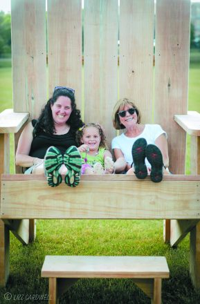 Three generations of Stephanie Harold's family sit together in the Big Chair before the concert.