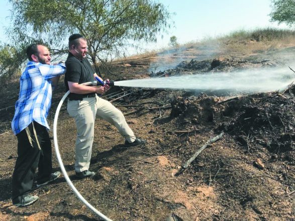 Noah and Yosef Klein of Oak Park helped put out a fire caused by a kite from Gaza when they visited IDF soldiers in July.