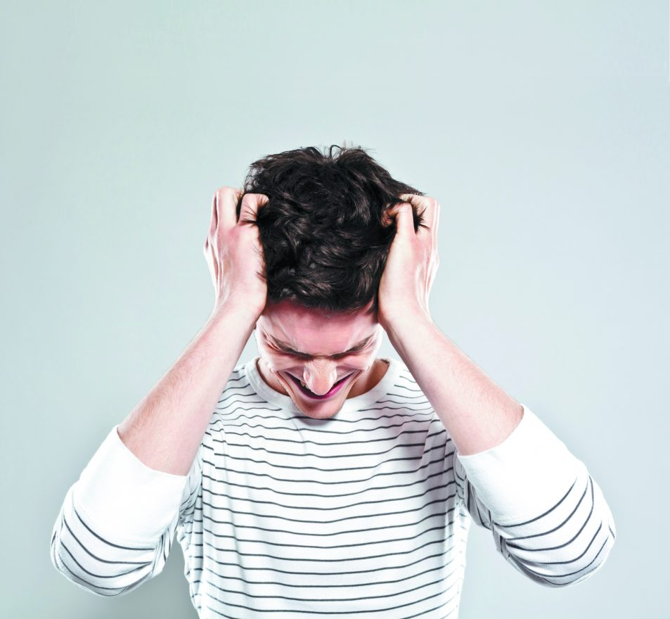 Portrait of desperate and stressed young man pulling his hair. Studio shot, grey background.
