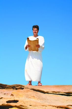 A man in a white robe reads from a scroll in a hot and sunny rocky desert landscape Shabbat Rosh Chodesh