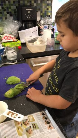 C cuts the avocado for the sushi rolls.