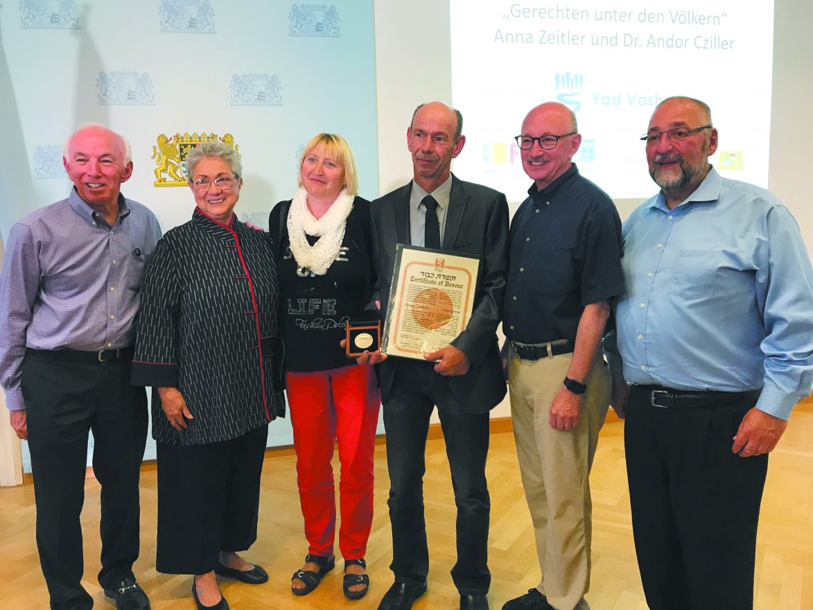 George Zeitler, grandson of Anna Zeitler, holds the certificate naming her a Righteous Among the Nations for saving two Jewish brothers during the Holocaust. From left to right: Abe Slaim, his cousin Bella Szlamkowicz Weberman, whose father was also hidden in the barn, Petra Zeitler, George Zeitler, John Slaim and his cousin Issac Szlamkowicz.