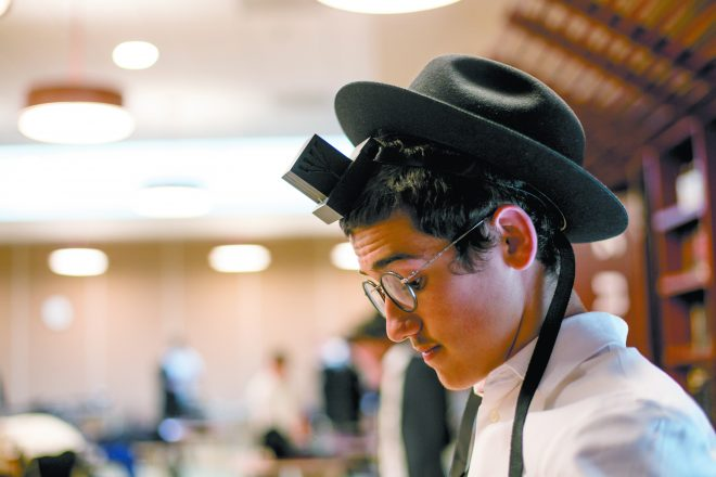Levi Uminer, 16, a student at the International School for Chabad Leadership in Oak Park, puts on tefillin as part of his morning routine.