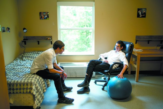 The teens, who are good friends, relax in the dorm room they shared this summer.