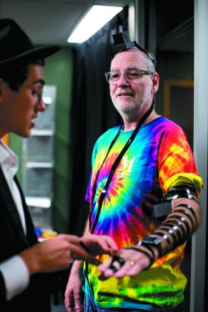Paul Stoloff, a visitor to photographer Marty Abrin's Southfield office, pays attention as Levi explains the importance of putting on tefillin.