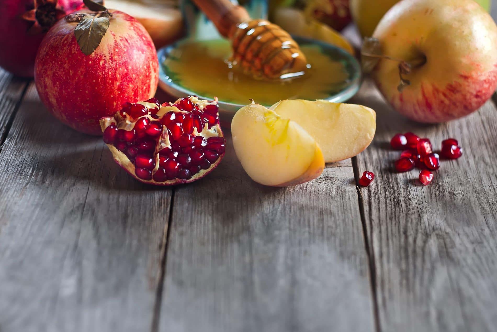Pomegranate, apple and honey, traditional food of jewish New Year celebration, Rosh Hashana. Selective focus. Copyspace background. Rosh Hashanah holiday food