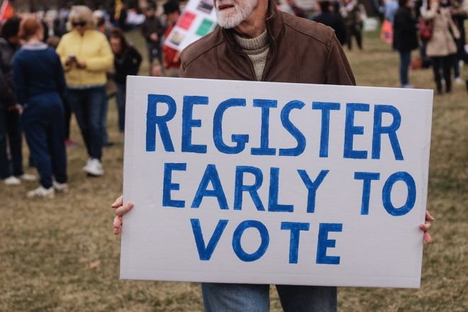 "Man holding a sign saying ""register early to vote,"" register to vote."