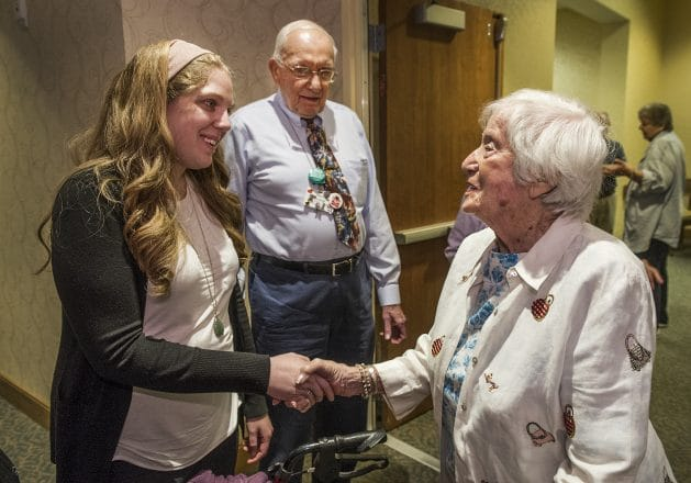 Aliza Tick, education associate with the HMC, shakes hands with 102-year-old Bertle Reis of Novi, who escaped the German occupation of Europe. President of the Shalom Club, Dr. Fred Bernstein, looks on.