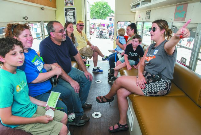 Brittany Feldman of Ferndale with Hazon, right, talks to a group inside Hazon's Topsy Turvy Bus, which runs on used vegetable oil.