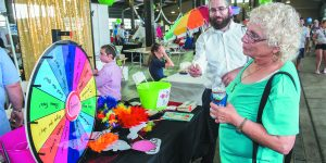 Judy Rosen of Southfield spins the wheel to see what she won as Bentzi Geisinsky of Chabad of Bingham Farms watches.