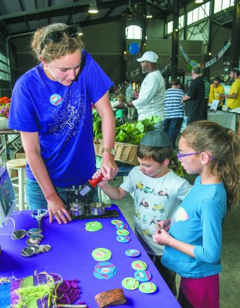 Friendship Circle member Jamie Reedholm of Berkley helps Aryeh Leyb Pinson, 5, and his sister Shayna Pinson, 8, both of Detroit, create a food button to wear.
