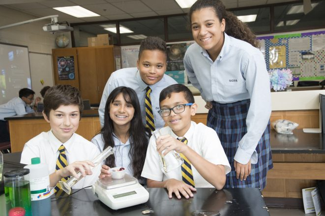 Detroit Country Day School (DCDS) students smile for the camera. Three students sit in front and two students stand behind as they work on a chemistry project.