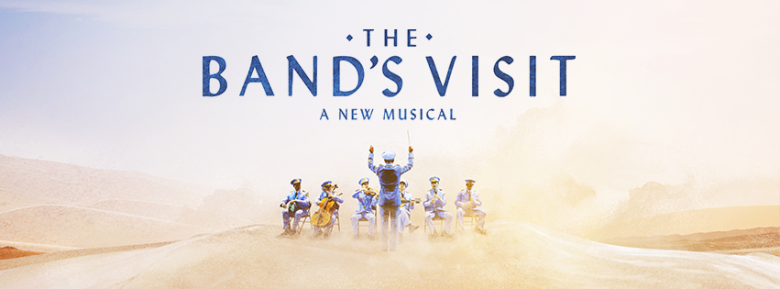 Poster for The Band's Visit - A New Musical with a band playing in the desert sand.